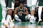 Milwaukee Bucks' Giannis Antetokounmpo sits on the floor after being knocked down during the third quarter of an NBA basketball game against the Boston Celtics Wednesday, Oct. 30, 2019, in Boston. (AP Photo/Winslow Townson)