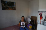 In this Feb. 13, 2020 photo, Alondra Mora holds a picture of her husband, Miguel Flores Lopez, 38, who disappeared Jan. 10, as she sits on the single bed the couple shared in the two-bedroom home where they lived with their four children, in Irapuato, Guanajuato state, Mexico. The Jalisco New Generation cartel is mounting a propaganda campaign in the area, using videos and social media to threaten rivals, while promising civilians that it won't prey on them with extortion and kidnappings. (AP Photo/Rebecca Blackwell)