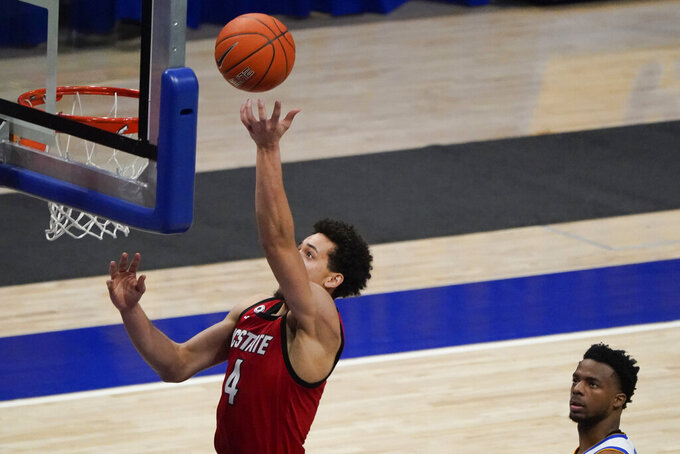 North Carolina State's Jericole Hellems (4) makes a basket after getting by Pittsburgh's Xavier Johnson (1) during the second half of an NCAA college basketball game, Wednesday, Feb. 17, 2021, in Pittsburgh. North Carolina State won 74-73. (AP Photo/Keith Srakocic)