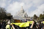 Protesters take part in a rally under the Basilica of Sacre Coeur in Montmartre, Paris Saturday, March 23, 2019. The French government vowed to strengthen security as yellow vest protesters stage a 19th round of demonstrations, in an effort to avoid a repeat of last week's riots in Paris. (AP Photo/Kamil Zihnioglu)