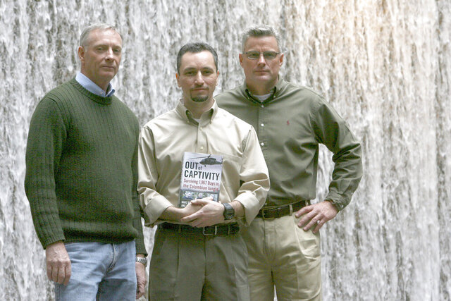 FILE - In this Feb. 26, 2009, file photo, former hostages, from left, Tom Howes, Marc Gonsalves and Keith Stansell pose for a portrait in New York. The American defense contractors held for years by leftist rebels in Colombia moved closer to collecting on a $318 million judgment against their former captors after the U.S. Supreme Court rejected a last-minute appeal by a sanctioned Venezuelan businessman whose assets they were seeking to claim. (AP Photo/Mary Altaffer, File)