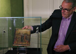 FILE - In this Tuesday, Sept. 24, 2019 filer, art expert Stephane Pinta takes out of a glass case a painting by Italian master Cimabue in Paris. A masterpiece attributed to the 13th-century Italian painter Cimabue that was discovered in an elderly French woman's kitchen is expected to sell for millions at auction. Stephane Pinta, a painting specialist with the Turquin gallery in Paris, said an auctioneer spotted the painting while inspecting the woman's house in Compiegne in northern France and suggested she bring it to experts for an evaluation. (AP Photo/Michel Euler)