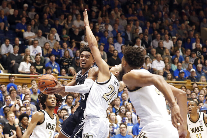Duke guard Tre Jones, front left, drives to the basket while Wake Forest guard Michael Wynn (20) defends during the second half of an NCAA college basketball game in Durham, N.C., Saturday, Jan. 11, 2020. (AP Photo/Gerry Broome)