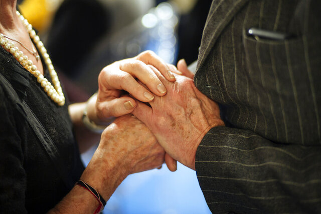 FILE - In this Dec. 23, 2019, file photo, French Shoah Museum president, Eric de Rothschild, right, holds the hand of a holocaust survivor during an event organized by the Conference on Jewish Material Claims Against Germany named 'Survivors Night' in Paris. The New York-based Conference on Jewish Material Claims Against Germany, an organization that handles claims on behalf of Jewish victims of the Nazis, said Monday, April 6, 2020, that the $4.3 million in initial funding was being distributed to reinforce an array of services provided by agencies around the world for some 120,000 survivors. (AP Photo/Kamil Zihnioglu, File)
