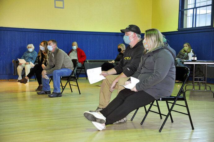 The parents of two Monroe school boys kicked off a school bus for not properly wearing masks attend a school board hearing on Monday, Oct. 12, 2020, in Monroe, N.H. The two elementary school students who were kicked off a school bus in New Hampshire last week for not keeping their faces covered will now be allowed to return on the bus. (Dana Gray/Caledonian-Record via AP)
