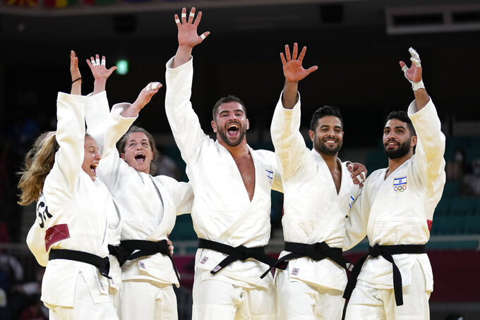 Members of Israel's team celebrate after defeating the Russian Olympic Committee team in their bronze medal match in team judo competition at the 2020 Summer Olympics, Saturday, July 31, 2021, in Tokyo, Japan. (AP Photo/Vincent Thian)