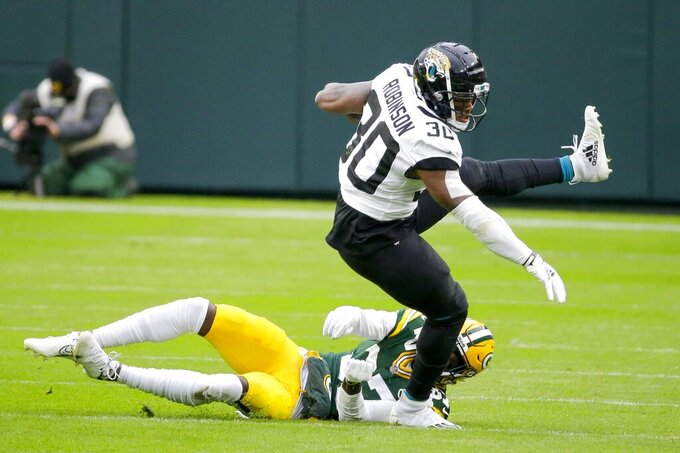 Jacksonville Jaguars' James Robinson gets past Green Bay Packers' Josh Jackson during the first half of an NFL football game Sunday, Nov. 15, 2020, in Green Bay, Wis. (AP Photo/Mike Roemer)