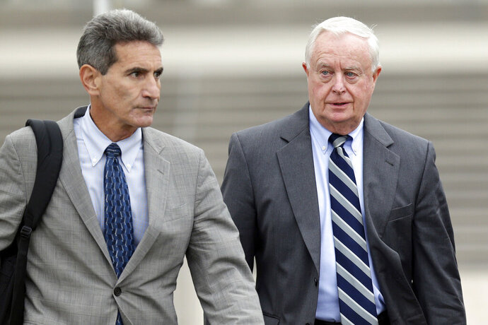FILE - This Oct. 25, 2017 file photo shows then - Suffolk County District Attorney Thomas Spota, right, and his attorney Alan Vinegrad leaving the courthouse in Central Islip, N.Y. Spota is accused of conspiring with the police chief and a top deputy in the DA's office to pressure witnesses to not cooperate with an FBI investigation into a 2012 assault.(AP Photo/Seth Wenig, File)
