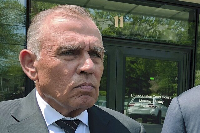 FILE - In this May 22, 2019, file photo, Ariel Quiros, left, former owner of Jay Peak Resort, stands outside the federal courthouse in Burlington, Vt., after his arraignment on fraud charges over a failed plan to build a biotechnology plant using foreign investors' money. The Miami businessman, accused of being the mastermind behind a massive fraud case involving foreign investors' money in Vermont developments, is expected to plead guilty in next week in a plea deal in which prosecutors are seeking a sentence of more than eight years in prison. (AP Photo/Lisa Rathke, File)