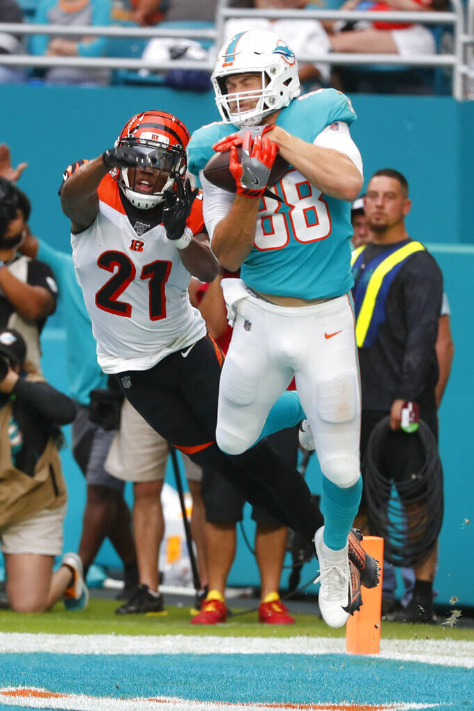 Miami Dolphins tight end Mike Gesicki (88) catches a pass in the enzone for a touchdown as Cincinnati Bengals defensive back Darqueze Dennard (21) attempts to defend, during the second half at an NFL football game, Sunday, Dec. 22, 2019, in Miami Gardens, Fla. (AP Photo/Wilfredo Lee)