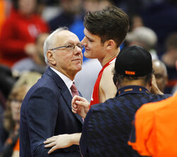 FILE - Syracuse head coach Jim Boeheim, left, congratulates his son, Cornell's Jimmy Boeheim, right, at the end of an NCAA college basketball game in Syracuse, N.Y., in this Friday, Nov. 10, 2017, file photo. Jimmy Boeheim is transferring to Syracuse to play for his father and with his younger brother after three seasons at Cornell. Coach Jim Boeheim's oldest son made the announcement Friday, April 16, 2021, on Instagram.  (AP Photo/Nick Lisi, File)
