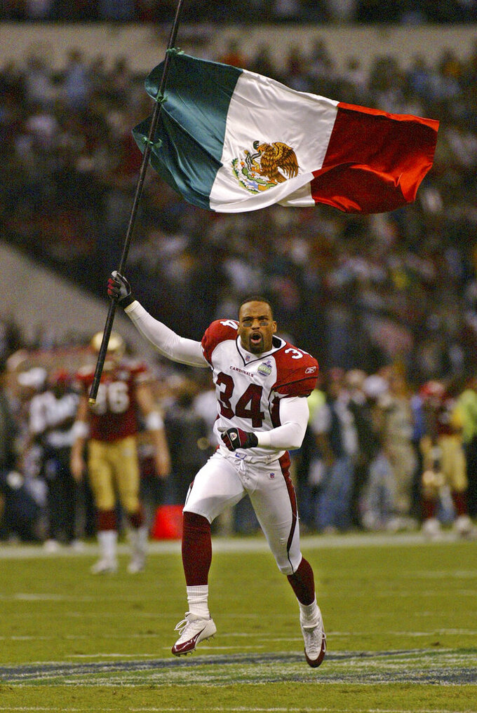 FILE - In this Oct. 2, 2005, file photo, Arizona Cardinals safety Robert Griffith enters the field holding a Mexican flag at Azteca Stadium in Mexico City, before the team's game agains the San Francisco 49ers. The NFL has held six games in Toronto and three in Mexico City. (AP Photo/Claudio Cruz, File)