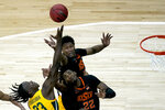 Baylor's Jonathan Tchamwa Tchatchoua battles Oklahoma State's Kalib Boone (22) and Matthew-Alexander Moncrieffe (12) for a rebound during the first half of an NCAA college basketball game in the semifinals of the Big 12 tournament in Kansas City, Mo., Friday, March 12, 2021. (AP Photo/Charlie Riedel)