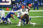 New York Giants' Wayne Gallman (22) rushes past Cleveland Browns' Myles Garrett (95) during the first half of an NFL football game, Sunday, Dec. 20, 2020, in East Rutherford, N.J. (AP Photo/Seth Wenig)