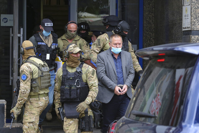 Hysni Gucati, the head of the War Veterans Organization of the Kosovo Liberation Army is escorted by European Union security police officers, from the offices of a war veterans association in Kosovo, in Pristina, Friday, Sept. 25, 2020. Witnesses say European Union security police have stormed the offices of a war veterans association in Kosovo. The association represents the former ethnic Albanian separatists who fought Serbian troops in a 1998-1999 war for independence. Members of the group said police from the European Union Rule of Law Mission in Kosovo, or EULEX, prevented them from going into the association's offices in Pristina on Friday.  (AP Photo/Visar Kryeziu)