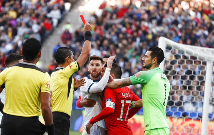 Argentina's Lionel Messi, center left, and Chile's Gary Medel, center right, scuffle as referee Mario Diaz, from Paraguay shows the red card to both of them during the Copa America third-place soccer match at the Arena Corinthians in Sao Paulo, Brazil, Saturday, July 6, 2019. (AP Photo/Victor R. Caivano)