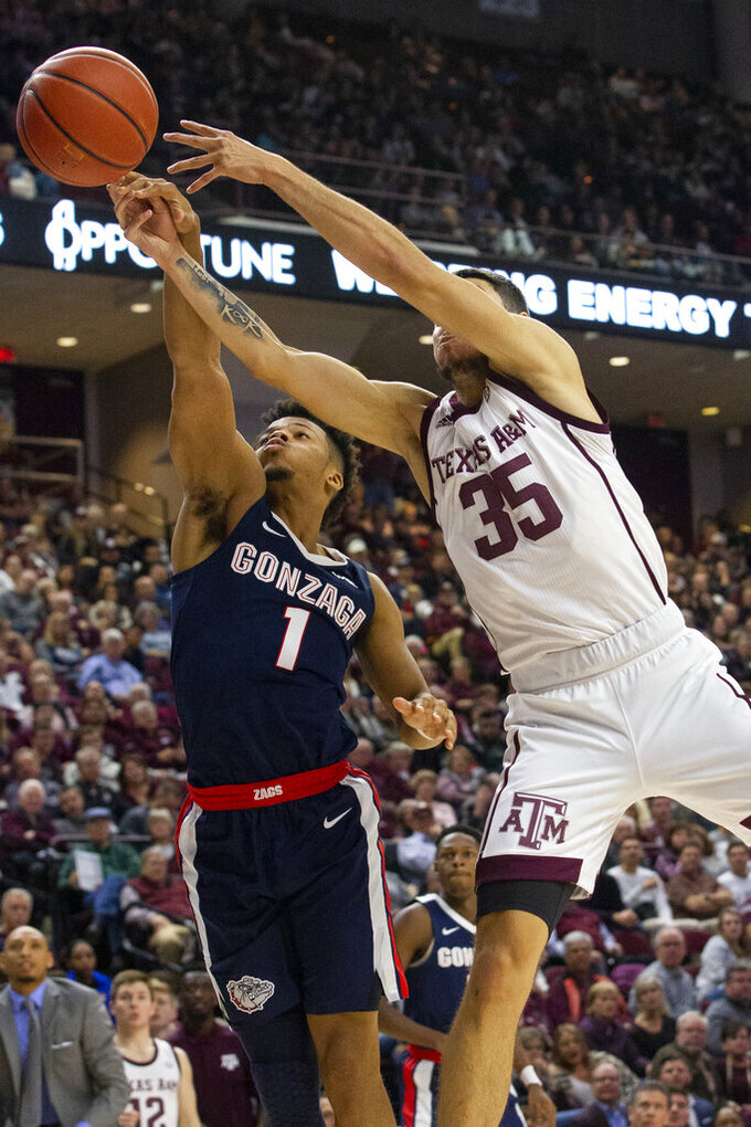 Texas A&M forward Yavuz Gultekin (35) and Gonzaga guard Admon Gilder (1) reach for the ball during the second half of an NCAA college basketball game Friday, Nov. 15, 2019, in College Station, Texas. (AP Photo/Sam Craft)