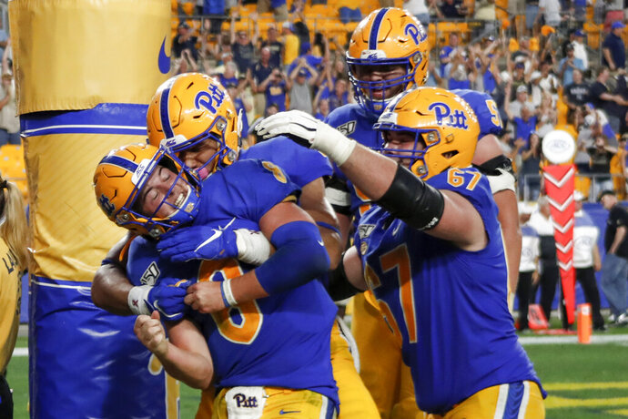 Pittsburgh quarterback Kenny Pickett (8) celebrates with teammates after he caught a pass for a touchdown against Central Florida during the second half of an NCAA college football game, Saturday, Sept. 21, 2019, in Pittsburgh.  (AP Photo/Keith Srakocic)