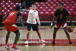 FILE - In this Oct. 15, 2019, file photo, Maryland men's coach Mark Turgeon, center, runs practice with Darryl Morsell, left, and Travis Valmon during media day for the team in College Park, Md. The NCAA Division I Council on Wednesday, June 17, 2020, approved a plan to allow college basketball players to start working with their coaches for the first time since the pandemic wiped out March Madness. The summer access period for men's and women's players will begin July 20. (AP Photo/Gail Burton, File)