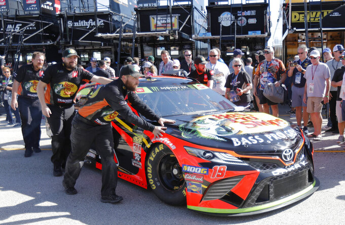 Crew members for Martin Truex Jr. move his car before practice for a NASCAR Cup Series auto race on Saturday, Nov. 16, 2019, at Homestead-Miami Speedway in Homestead, Fla. Truex one of four drivers racing for the championship. (AP Photo/Terry Renna)