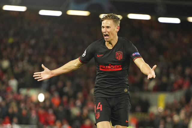 Atletico Madrid's Marcos Llorente, right, celebrates after scoring his side's second goal during a second leg, round of 16, Champions League soccer match between Liverpool and Atletico Madrid at Anfield stadium in Liverpool, England, Wednesday, March 11, 2020. (AP Photo/Jon Super)