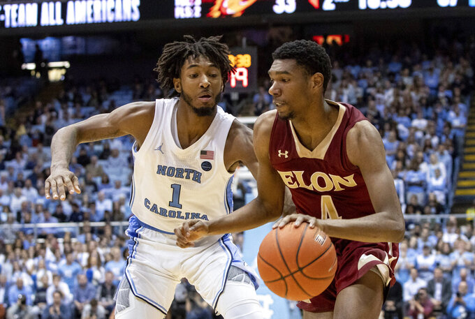 Elon's Marcus Sheffield II (4) drives as North Carolina's Leaky Black (1) defends during the second half of an NCAA college basketball game in Chapel Hill, N.C., Wednesday, Nov. 20, 2019. (AP Photo/Ben McKeown)