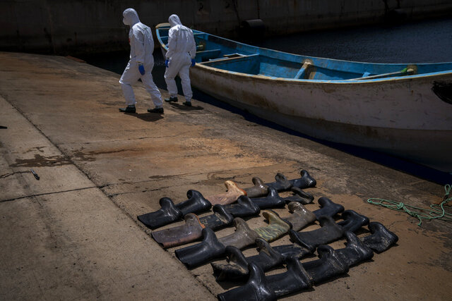Waterproof boots are placed on the ground by police officers as they inspect a boat where 15 Malians were found dead adrift in the Atlantic on Thursday, Aug. 20, 2020 in Gran Canaria island, Spain. (AP Photo/Emilio Morenatti)