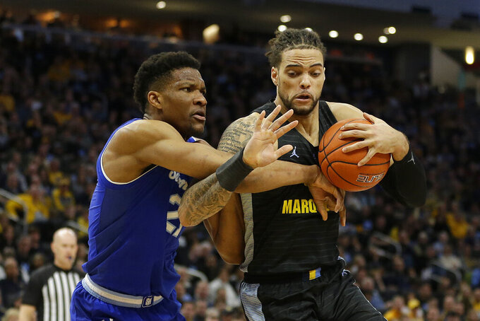 Marquette's Theo John, right drives to the basket against Seton Hall's Ike Obiagu during the first half of an NCAA college basketball game Saturday, Feb. 29, 2020, in Milwaukee. (AP Photo/Aaron Gash)