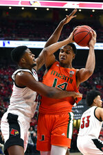 Miami center Rodney Miller Jr. (14) attempts to keep the ball away from Louisville center Steven Enoch during the first half of an NCAA college basketball game in Louisville, Ky., Tuesday, Jan. 7, 2020. (AP Photo/Timothy D. Easley)