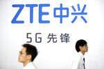 FILE - In this Sept. 26, 2018, file photo, visitors walk beneath the logo of Chinese technology firm ZTE at the PT Expo in Beijing.  The Federal Communications Commission on Friday, Nov. 22, 2019 voted, 5-0, to bar U.S. telecommunications providers from using government subsidies to pay for networking equipment from companies that are a threat to national security. The agency says China's Huawei and ZTE pose such a threat. (AP Photo/Mark Schiefelbein, File)