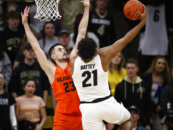 Colorado forward Evan Battey, right, puts up a hook shot for a basket over Oregon State center Gligorije Rakocevic in the first half of an NCAA college basketball game Thursday, Jan. 31, 2019, in Boulder, Colo. (AP Photo/David Zalubowski)