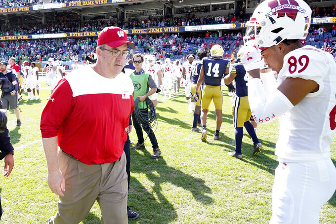 Wisconsin head coach Paul Chryst, left and A.J. Abbott walk off the field after the team's 41-13 loss to Notre Dame after an NCAA college football game Saturday, Sept. 25, 2021, in Chicago. (AP Photo/Charles Rex Arbogast)
