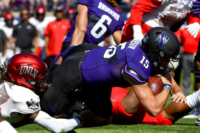 Northwestern quarterback Hunter Johnson (15) scores a touchdown against UNLV defensive back Evan Austrie, left, during the first half of an NCAA college football game, Saturday, Sept. 14, 2019, in Evanston, Ill. (AP Photo/Matt Marton)