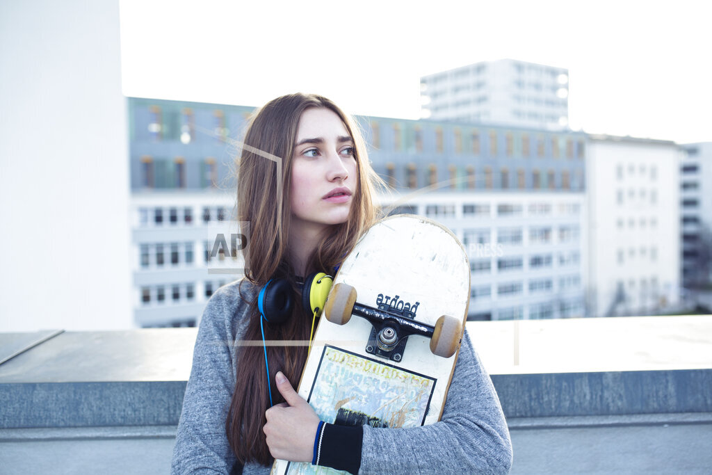 Serious young woman with skateboard and headphones in the city looking sideways