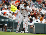 San Francisco Giants' Donovan Solano, front, gestures as he circles the bases after hitting a solo home run off Colorado Rockies starting pitcher Jon Gray in the sixth inning of a baseball game Wednesday, July 17, 2019, in Denver. San Francisco Giants third base coach Ron Wotus, back, looks on. (AP Photo/David Zalubowski)