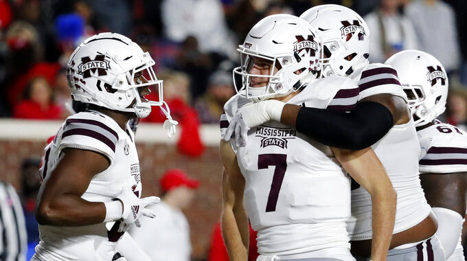 Mississippi State quarterback Nick Fitzgerald (7) is congratulated by teammates following an 8-yard touchdown run against Mississippi during the first half of an NCAA college football game in Oxford, Miss., Thursday, Nov. 22, 2018. (AP Photo/Rogelio V. Solis)