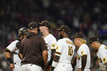 San Diego Padres starting pitcher Blake Snell, third from left, talks with interim pitching coach Ben Fritz, second from left, and teammates during the seventh inning of a baseball game against the Los Angeles Angels, Tuesday, Sept. 7, 2021, in San Diego. (AP Photo/Gregory Bull)
