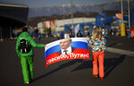 FILE - In this Feb. 23, 2014 file photo Veleriya Obarevich, right, and Yan Shamilov carry a Russian flag with the message