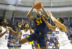West Virginia forward Oscar Tshiebwe (34) pulls down a rebound as TCU defenders Kevin Samuel (21), PJ Fuller (4) and Desmond Bane (1) look on during the first half of an NCAA college basketball game, Saturday, Feb. 22, 2020 in Fort Worth, Texas. (AP Photo/Ron Jenkins)