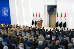 In this photo released by the official Facebook page of the Syrian Presidency, Syrian President Bashar Assad takes the oath of office for a fourth seven-year term, at the Syrian Presidential Palace in the capital Damascus, Syria, Saturday, July 17, 2021. In power since 2000, Assad's re-election in a landslide was not in doubt. His new term starts with the country still devastated by the 10-year war and sliding deeper into a worsening economic crisis. (Syrian Presidency via Facebook via AP)