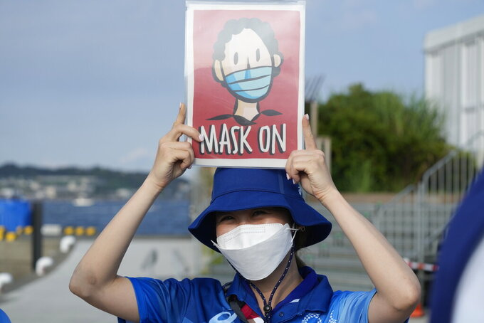 FILE - In this Aug. 1, 2021, file photo, Olympic volunteer Reimi Kusunoki holds up a sign at the Enoshima yacht harbor during the 2020 Summer Olympics in Fujisawa, Japan. Tokyo Olympians are exercising extraordinary discipline against the coronavirus. They are sealed off in a sanitary bubble that has made competition possible but is also squeezing a lot of fun from their Olympic experience. (AP Photo/Gregorio Borgia, File)