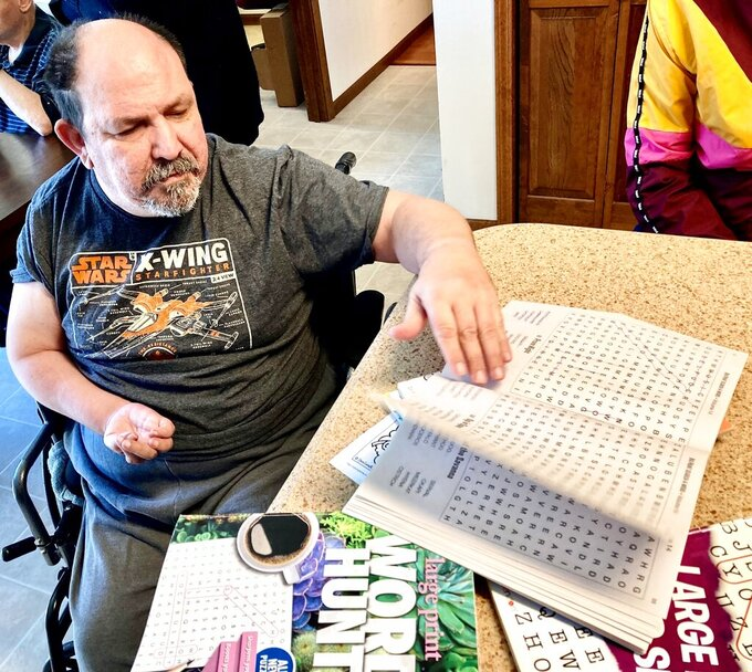 Mark S., shows some of the word search books he enjoys in this April 1, 2021 photo at his Springfield, Ill., group home operated by Sparc, an agency that assists people with intellectual and developmental disabilities. A state study prompted by a federal consent decree reports that it would cost the state $329 million this year alone to meet the 2011 court order's demands expanded community-based housing, training and the reduction of a list of 18,000 awaiting services. Sparc is prohibited by law from releasing full names of its residents. (AP Photo by John O'Connor)