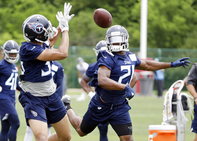 Tennessee Titans defensive back Malcolm Butler (21) knocks the ball away from defensive back Jeremy Boykins, left, during NFL football minicamp, Wednesday, June 13, 2018, in Nashville, Tenn. The Titans upgraded their secondary by signing Butler, and safety Kevin Byard is coming off an All-Pro season. Mix in veteran Logan Ryan and Adoree Jackson going into their second seasons together, and it's a group with high expectations for the season. (AP Photo/Mark Humphrey)