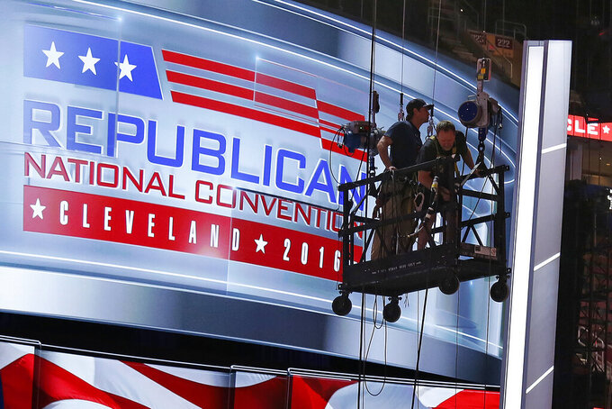 FILE - In this July 13, 2016, file photo the main stage on the convention floor at the Quicken Loans Arena in downtown Cleveland, Ohio, is prepared for the upcoming Republican National Convention, as workers stand in a man lift. The coronavirus pandemic is forcing Democrats and Republicans to take a close look at whether they'll be able to move forward as planned this summer with conventions that typically kick off the general election season. (AP Photo/Gene J. Puskar, File)