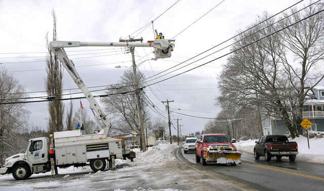 Utility crews work to restore power Sunday, Dec. 6, 2020, on Main Street in Greenwood, Maine, where the majority of Central Maine Power customers were without power after the first major winter storm of the season brought heavy, wet snow and high winds to the region.  (Andree Kehn/Sun Journal via AP)
