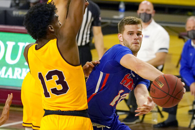 Houston Baptist guard Ty Dalton, right, passes the ball around Arizona State guard Josh Christopher (13) during the second half of an NCAA college basketball game, Sunday, Nov. 29, 2020, in Tempe, Ariz. (AP Photo/Rick Scuteri)