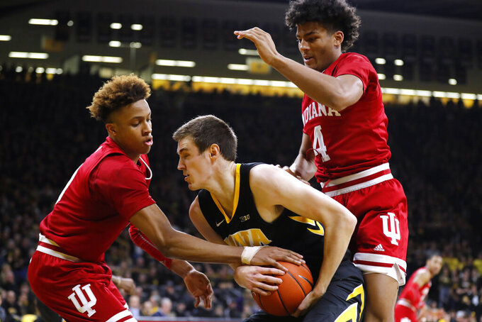 Iowa forward Nicholas Baer, center, grabs a rebound between Indiana's Romeo Langford, left, and Jake Forrester during the first half of an NCAA college basketball game Friday, Feb. 22, 2019, in Iowa City, Iowa. (AP Photo/Charlie Neibergall)