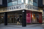 A man wearing a face mask walks past the Debenhams flagship department store on Oxford Street, during England's second coronavirus lockdown in London, Tuesday, Dec. 1, 2020. In another dark day for the British retailing industry, Debenhams said Tuesday it will start liquidating its business after a potential buyer of the company pulled out, a move that looks like it will cost 12,000 workers their jobs. (AP Photo/Matt Dunham)