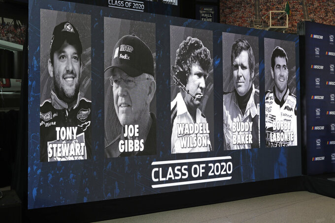 FILE - In this May 22, 2019, file photo, images of NASCAR's Hall of Fame Class of 2020, from left, Tony Stewart, Joe Gibbs, Waddell Wilson, Buddy Baker and Bobby Labonte are shown on a screen after an announcement in Charlotte, N.C. (AP Photo/Chuck Burton, File)
