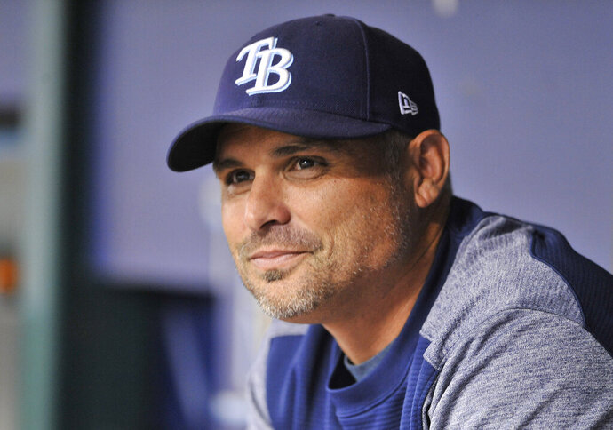 FILE - In this Aug. 23, 2018, file photo, Tampa Bay Rays manager Kevin Cash sits in the dugout before a baseball game against the Kansas City Royals, in St. Petersburg, Fla. Cash's team was one of the feel-good stories of 2018, improving by 10 victories despite undergoing a massive makeover that purged salary and ignited a youth-driven, second-half turnaround that kept Tampa Bay in contention for a postseason berth until late September. (AP Photo/Steve Nesius, File)